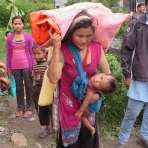 Lady facing a 3 hour walk uphill with baby and 40kg of supplies